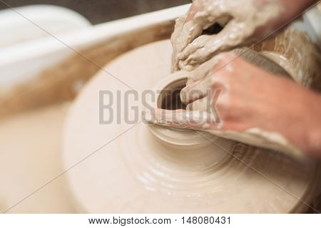 Pottery classes, student making clay pot on wheel. Close-up of dirty hands, sculpting clay crockery