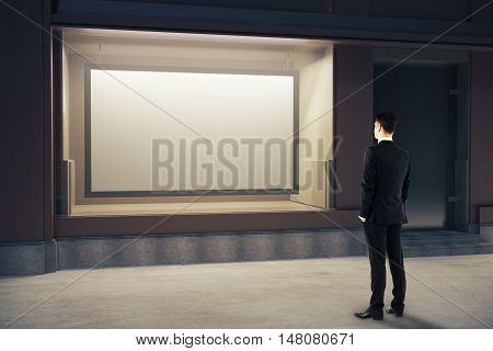 Man Looking At Billboard Inside Showcase