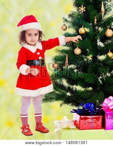 Adorable little curly-haired girl, dressed as Santa Claus decorates a Christmas tree toys.Bright, floral yellow-green blurred background.
