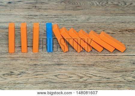 Blue wooden block among the orange stop the domino effect standing on an old wood table