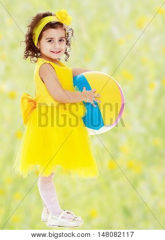 Laughing little girl in a bright yellow dress and bow on her head holding the ball. Girl posing sideways to the camera in full growth.Bright, floral yellow-green blurred background.