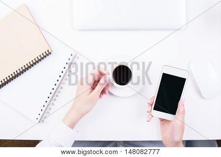 Top view of woman's hands holding coffee cup and blank cellular phone on office desktop with notepads closed laptop and other items. Mock up