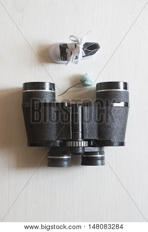 travel or vacation concept, old binoculars and flower on a white table