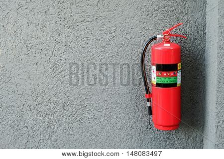 Fire extinguisher on the gray cement wall.
