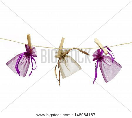 Three colored little gift bags hanging on a string with clothespins. Isolated on white background.