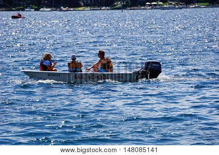 HARBOR SPRINGS, MICHIGAN / UNITED STATES - AUGUST 1, 2016: Teachers of the Little Traverse Sailors sailing school ride a motorboat in Little Traverse Bay.
