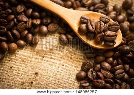 coffee beans on sackcloth and on a wooden spoon.