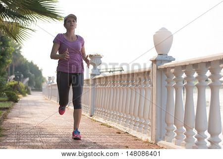 sporty woman jogging on sidewalk at early morning