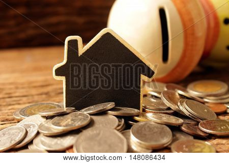 many coins with wood house concept idea save for purshase house.