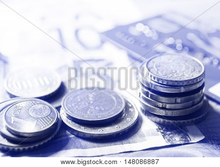 euros bank note and small change on the desktoned
