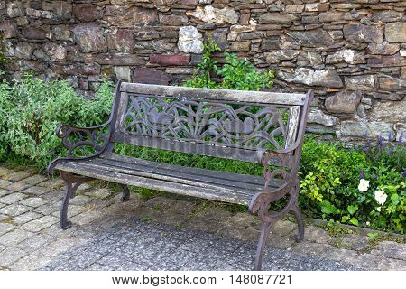 wrought iron bench with ornament on background of stone wall