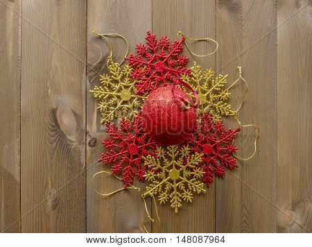 Group of shiny Christmas tree decorations lay flat on wooden background. Red and gold glitter snowflakes in circle with one red bauble in center