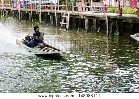 Bangkok Thailand - July 19, 2016 : Long tailed boat at engine speed of traffic on the canal in Bangkok.