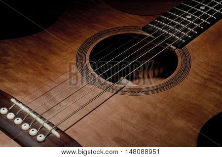 Close-up shot of mahogany guitar's features and sound hole