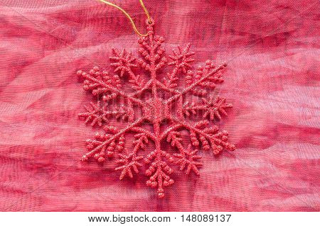 Single red glitter snowflake Christmas tree decoration lay flat on red cloth background