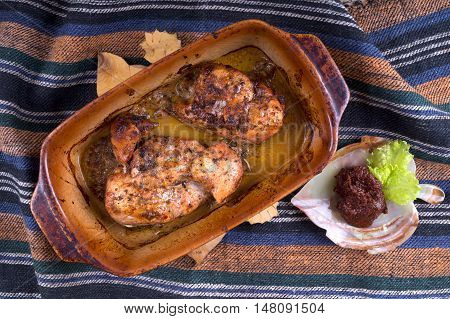 Roast in pottery with sauce and greens on a hand-woven fabrics