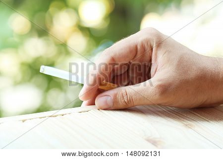 Male hand holding a cigarette, close up