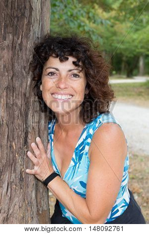 Middle-aged Woman On A Tree In Summer Park