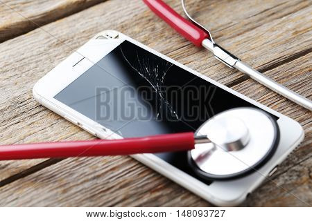 Broken Smartphone With Stethoscope On A Grey Wooden Table