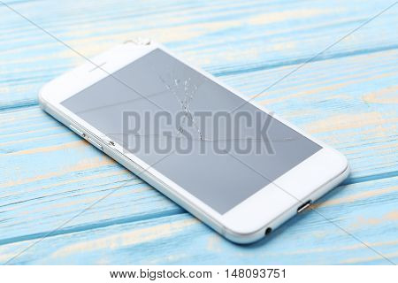 Broken Smartphone On A Blue Wooden Table
