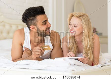 Young Couple Lying In Bed Using Tablet Computer Hold Credit card Online Shopping Payment, Happy Smiling Hispanic Man And Woman Lovers In Bedroom