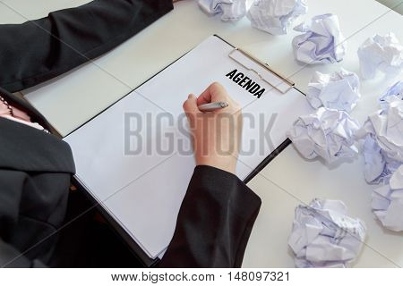 Hands of female writing agenda with crumple sheets of papers at the office desk.