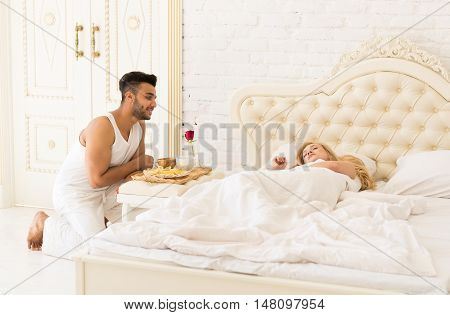 Hispanic Man Bring Breakfast To Sleeping Woman In Morning Tray With Red Rose Flower, Young Couple Lovers In Bedroom