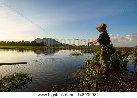 An Angler Wearing Old Hat Was Fishing By The Lakeside Alone.