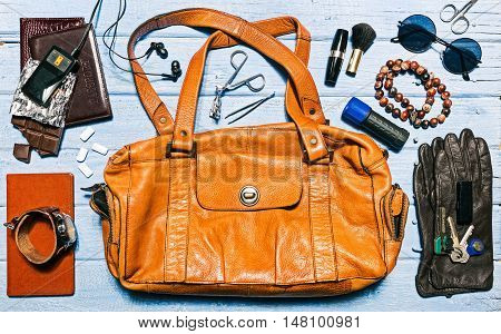 Contents of modern woman bag: female accessories on the blue planked surface. Flat lay. Color toning