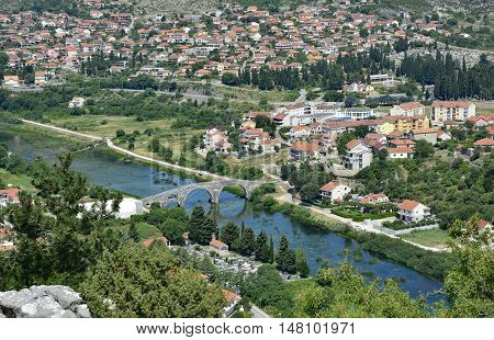 An aerial shot of the town of Trebinje in Bosnia taken from Crkvina Hill showing the historic 16th century Ottoman Arslanagica Most bridge over the Trebisnjica River.