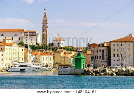 PIRAN SLOVENIA - AUGUST 30 2016: Piran marina with fishing boats and old town in background one of major tourist attractions on Slovenia's Adriatic coast