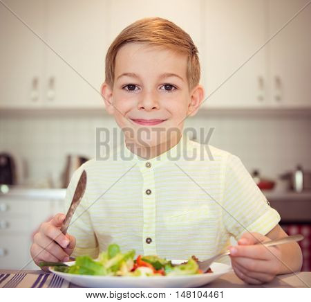 Young Diligent Boy  At A Table Eating Healthy Meal With Cutlery