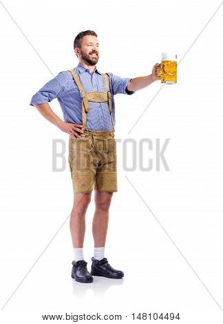 Handsome hipster young man in traditional bavarian clothes holding a mug of beer, clinking. Arm on hip. Oktoberfest. Studio shot on white background, isolated.