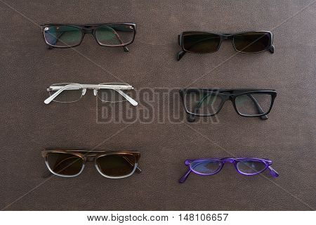 Collection of glasses and sunglasses on faux leather
