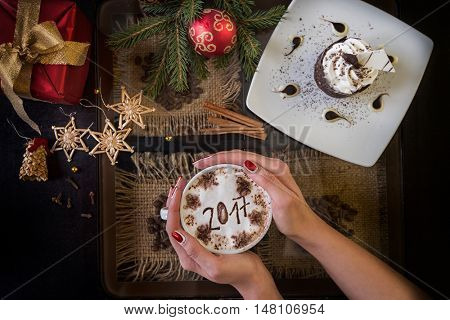 Hands holding mug of coffee close-up, on new year background