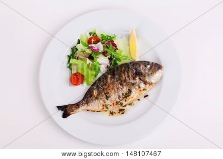 baked whole fish grilled on a plate with vegetables and lemon on top for the menu