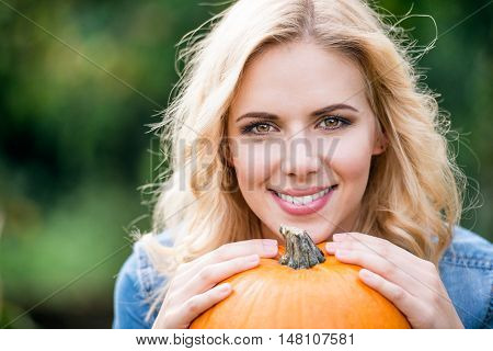 Close up of beautiful young blond woman in denim shirt with orange pumpkin. Autumn nature.