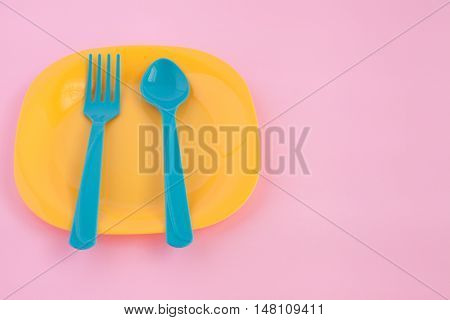 fork and spoon put on colorful plastic plate with pink background