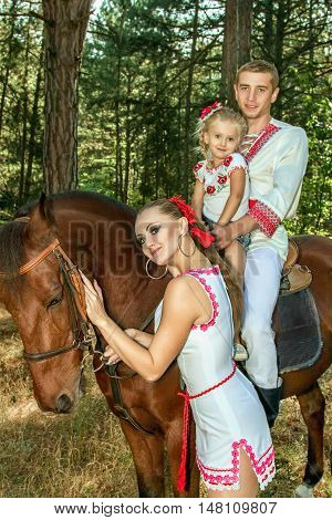 a Ukrainians mom and dad daughter ride in the woods on horseback