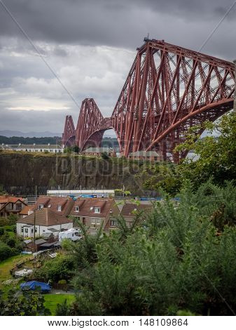 Homes under the Forth Rail Bridge at dusk in Edinburgh, Scotland, connecting the towns of North and South Queensferry