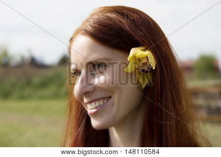 Beautiful woman with flower in her hair. Smiling face with freckles. Nice redhead girl. Portrait of young woman.