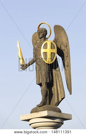 Statue of Saint Michael the Archangel with golden sword and shield near Holy Transfiguration Cathedral in Donetsk Ukraine - 2016 September 11. Close up. Сlear blue sky in the background.