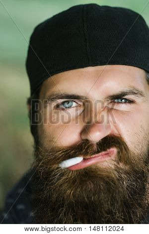 Young man hipster with moustache and long beard on handsome face with grimace in black cap smoking cigarette in his mouth closeup