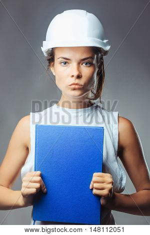 Young woman forewoman engineer with serious pretty face in building white helmet holding blue exercise book posing on grey background studio