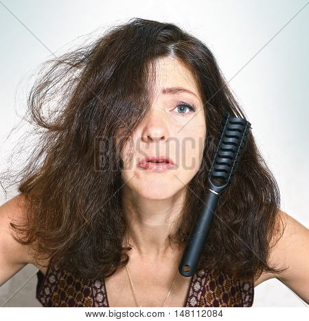 pretty young woman with brush comb stuck in her thick brown hair close up portrait