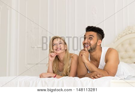 Young Couple Lying In Bed, Happy Smile Hispanic Man And Woman Lovers In Bedroom Looking Up To Copy Space