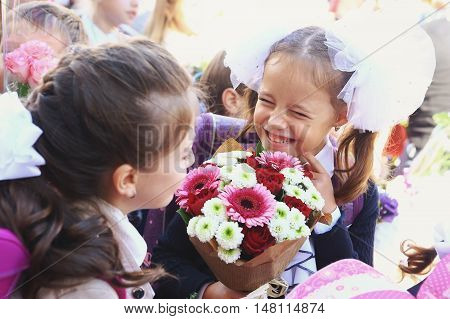 Moscow, Russia - September 1, 2016: Unidentified girls with flowers bouquet on solemn meeting of first grade kids, called the Day of Knowledge, signify the beginning of school year.