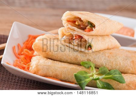 Vegetable spring rolls with dip sauce on wooden table.