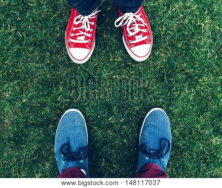 Youth sneakers on girl and boy legs on grass during sunny serene summer day
