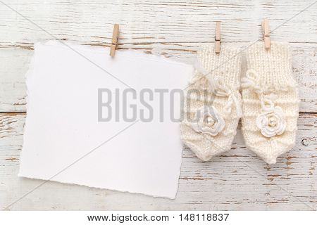 Baby New Born or baptism Greeting Card. Blank card with baby girl gloves on white wooden background.